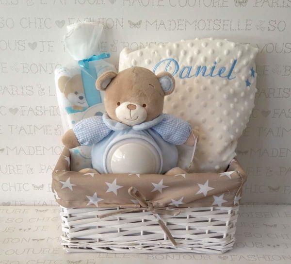 canastilla de bebé original con nombre bordado, peluche, manta y gasas.
